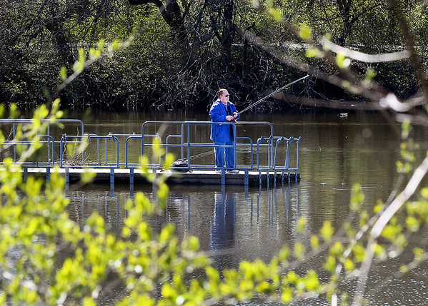John P. Cleary | The Herald Bulletin <br /> This fisherman is framed by the budding trees and bushes along the banks of Shadyside Lake as he casts his luck from the pier at the activities center Monday afternoon.