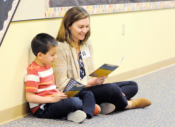 Don Knight | The Herald Bulletin<br /> Elizabeth Imafuji reads a book with her son Lucas, 7, while volunteering in his class at Eastside Elementary on Tuesday.