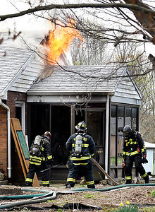 Firefighters wait to get water from the tankers as flames break through the attic area of this house fire in the 200 block of County Road 650 North Tuesday morning. Firefighters from multiple agencies were dispatched to battle the blaze.