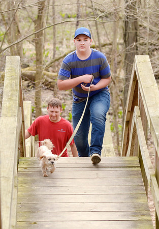 Canaan Troyer walks the family dog Moose up a set of stairs as followed by his father Merlin on a family outing on trail 2 at Mounds State Park.