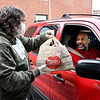 First Church of the Nazarene staff member Keri Kardatzke hands out a bag of essential household items to these folks as they drove up to the church doors Wednesday. The church was distributing items like paper towels, toilet paper, and toothpaste to the public.