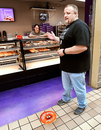 Mark Bowers, co-owner of Jack's Donuts, explains the donut decal on the floor is the safe distance to be from Stephanie Dyer at the counter while she takes and fills your order. For their carry-out customers at the 1909 University Blvd. location they have the donut decals spaced 6-feet apart through the shop.