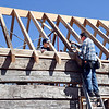 Jay Moore and Steve Wills work on the rafters Thursday for the roof of the old log cabin being rebuilt at the north entrance to Falls Park in Pendleton. The rafters came from a large poplar tree that stood near the old Carnegie Library building in town.