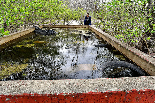 The former ALAC Laundry property still has this concrete containment structure that now holds about 18 inches of water that is filled with trash and tires. Area resident Tess Etchison says it's a breeding ground for mosquitoes.