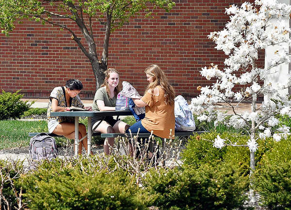 As the temperature rose to almost 80 degrees Tuesday, people got outside to enjoy the beautiful spring day like these ladies sitting outside of Decker Hall at Anderson University taking in the warm sunshine and the flowering trees.