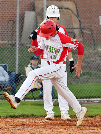 Anderson's Conner Stephenson high-steps it home as he scores on a past ball in the first inning where the Indians scored 9 runs.