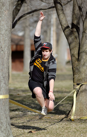 Anderson University senior Isaac Vining keeps his balance as he walks along a nylon strap that is tethered between trees on the AU campus Thursday afternoon.  Vining and several of his classmates say they practice this balancing act as a way to relax and relieve the tensions of the day, and also enjoy the nicer weather.