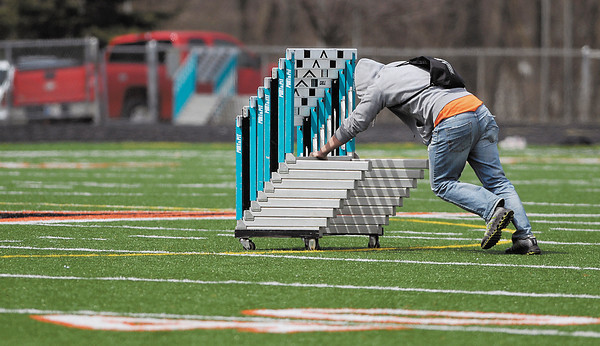 AU sophomore Kyle Green had a hard time pushing this rack of hurdles across the football field after the AU Invitational Track & Field meet was over finding the shortcut wasn't the easiest path.