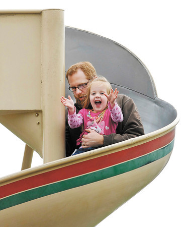 3 year old Claire Callahan reacts with joy as her father, DJ Callahan, takes her down the large circular slide in the playground at Shadyside Lake Monday afternoon.  The Callahan family was out at the park enjoying a pleasant, warm afternoon.