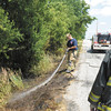 Jordan Allen and Lt. Robert Wagner from the Richland Township Volunteer Fire Department douse the scene of a grass fire on County Road 700 North east of Indiana 9 on Tuesday. Alexandria's fire department made the initial knock down of the fire after conflicting calls first reported the fire at CR 900 North.