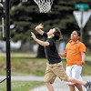 Kyler Lynn, 13, drives to the basket around Venice McCullough, 12, Monday after school as they play in a neighborhood pick-up game along Fairview Street in the Meadowbrook addition.  With the temperatures finally climbing to above normal folks are getting the spring fever.
