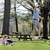 While Sarah Needham enjoys reading her book while laying in the warm sunshine her husband Scott works on his balancing act on  a tie-down strap between two trees at Mounds State Park Monday afternoon.  The Needhams, from Upland, IN., were taking the day to enjoy the nice weather, the park, and a picnic.