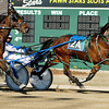 Ed Hensley looks over as Past The Shooter comes on at the wire in the second race on opening night of live racing at Hoosier Park.  Hensley, driving Sand Burner, held on and won the race.