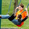 Zachary Hilgeman, 12, finds straddling two swings a bit more challenging  then just the normal swinging method as he plays on the playground at Pulaski Park Friday afternoon with family.    Zachary is from the Dominican Republic and was in Anderson visiting relatives.  <br /> To purchase this photo or other photos produced by The Herald Bulletin<br /> staff, visit heraldbulletin.smugmug.com.