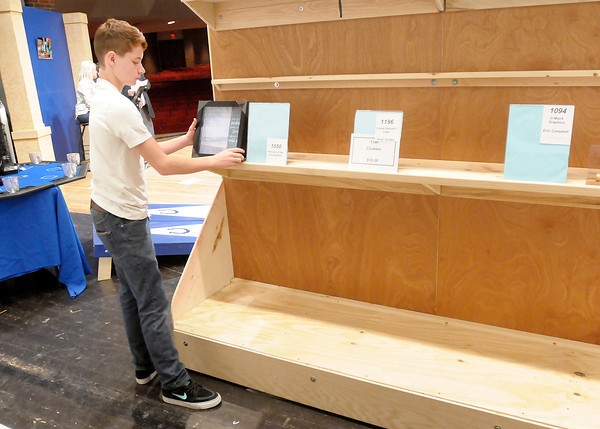 Casey Sowash, 14, puts out new items during the Bids for Kids Auction at Reardon Auditorium on Friday. To purchase this photo or other photos produced by The Herald Bulletin staff, visit heraldbulletin.smugmug.com.