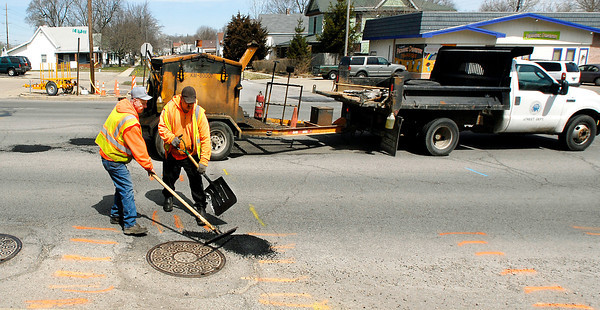 Anderson Street Department workers Fred Steffler and Rick Streaty were putting down hot patch mix as they were filling potholes along east 8th Street Thursday afternoon.