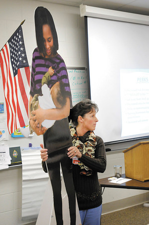 RN Elizabeth Arnett holds up a lifesize cutout of student Mia Fuller and her son Kaiden as she tells students about the benefits of breast feeding at Anderson High School on Friday.