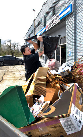 Adam Anderson, owner of Anderson Street Concepts, 1504 North B Street, Elwood, throws another bag of trash into the dumpster outside his business as he tries to cleanup after the flooding that hit Elwood last Friday.  Anderson says he has filled up three dumpsters so far with a long way to go before he's done.   <br /> To purchase this photo or other photos produced by The Herald Bulletin<br /> staff, visit heraldbulletin.smugmug.com.