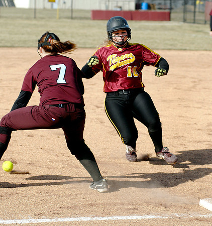 Alexandria's Hannah Murphy starts to slide into third as Wes-Del's Taylor Ward goes after the low throw during their softball game Wednesday.  Murphy was safe and scored as the ball got away from Ward.