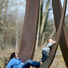 Daisha Carnahan, 19, helps her 5 year old nephew Carmine Douglas try to climb up the side of one of the metal sculptures at Shadyside Lake Wednesday.  With warmer temperatures, people were getting out to enjoy the spring-like weather.