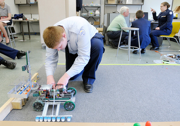 Quinton Stamm, 15, installs batteries in the APA Robotics team's robot as the team met to work on their project after school.