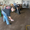 Daniel White starts to spray more disinfectant  on the carpet as Adam Anderson positions the drying fans as they cleanup after the Elwood flooding of last Friday at Anderson's business, Anderson Street Concepts at 1504 North B Street in Elwood.<br /> To purchase this photo or other photos produced by The Herald Bulletin<br /> staff, visit heraldbulletin.smugmug.com.