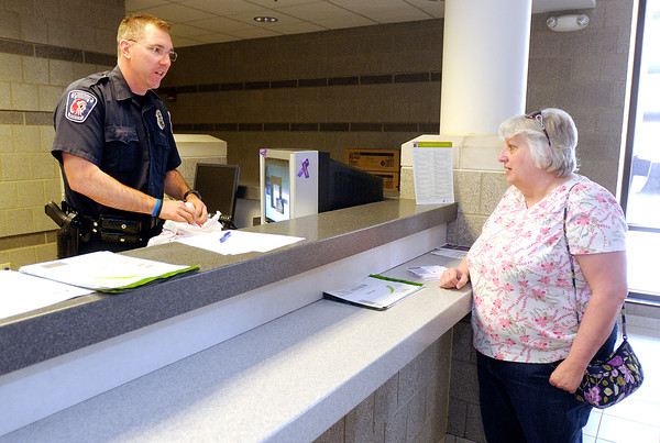APD officer Brad McClain accepts unused prescription drugs from Debbie Hall at the police department on Saturday during the Safe-Drug Drop-Off.