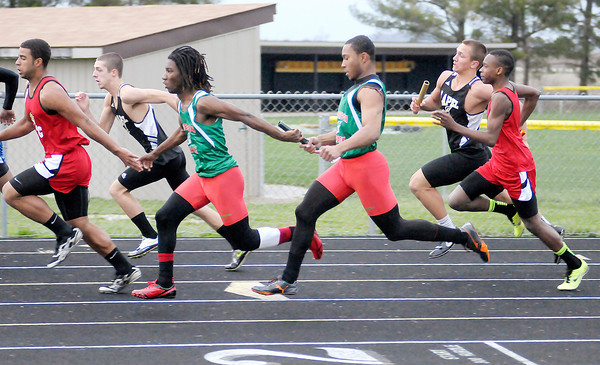 Anderson's Dorian Wilson hands the baton to Nakosh Chamberlain during the 4 by 100 meter relay during the Madison County Track Tournament at Madison-Grant on Friday.