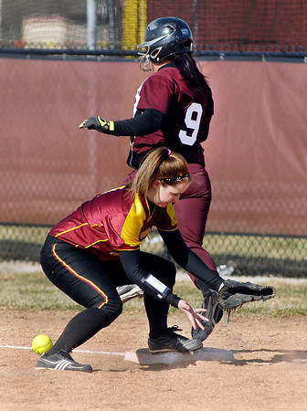 The ball  gets by Alexandria's Jordan Goodman at first base as the Wes-Del batter Courtnee Kirtley crosses the bag on a bunt play.