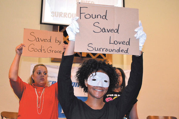 Churchgoers display their personal testimony signs during Easter service at Celebration Church, 1120 Arrow Ave., Sunday morning.