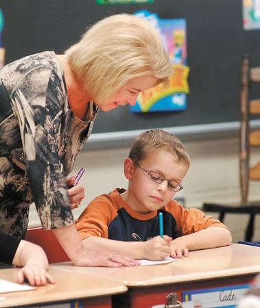 Pendleton Elmentary School 3rd grade teacher Connie Broughton checks on Cade Riffey and his cursive writing.