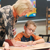 Pendleton Elmentary School 3rd grade teacher Connie Broughton checks on Cade Riffey and his cursive writing.