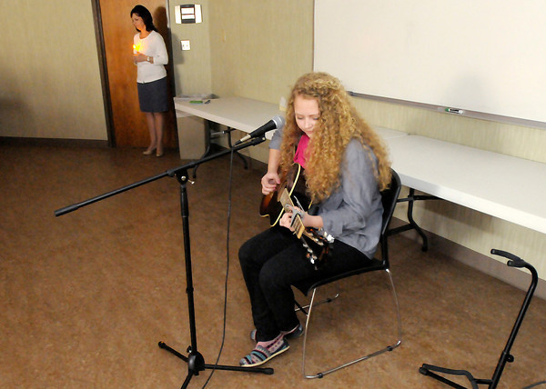"""Pendleton Heights' sophomore Emily Callen performs her original song """"20 Angels"""" as Aspire held a candle light vigil on Tuesday as part of child abuse awareness month. Callen was inspired to write her song in the wake of the Newtown Connecticut shootings."""