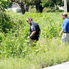 Officers search along West 8th Street for evidence after capturing a suspect in the robbery of the PNC on Nichol Avenue in a bean field on 8th Street. APD K9 Magnum was shot trying to capture the suspect.