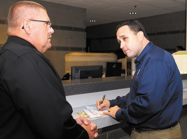 Anderson Police Chief Larry Crenshaw talks with David Myers, vice president of business development for F.E. Moran, Inc., as he writes out a $19,000 check to the department's K-9 fund Monday morning to help replace the two dogs that have died in the line of duty recently.