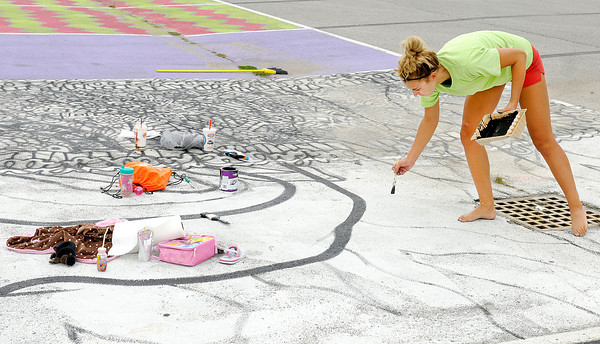 Esther Mishler, 17, outlines the design for her senior parking space. Mishler and Alexa Morris combined their spaces for a larger canvas. Seniors painting their parking spaces to reflect their own style and personality is a tradition at Anderson High School.