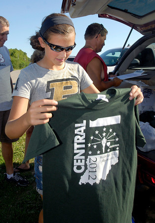 Riverfield Little League softball team member Brinkley Gary checks out the Central Regional championship t-shirts that were passed out Monday as the team prepared to leave for Portland, Oregon for the Little League Softball World Series.