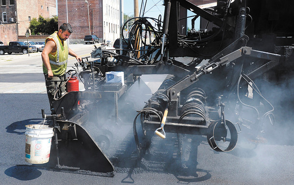 Tony Drousias from Gallagher Asphalt operates a paving machines as Meridian Street is resurfaced by recycling the asphalt that is already in place.