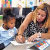 Kaliyah Spratt watches as paraeducator April Schindler helps her print her name at Kindergarten Camp at Anderson Elementary School.