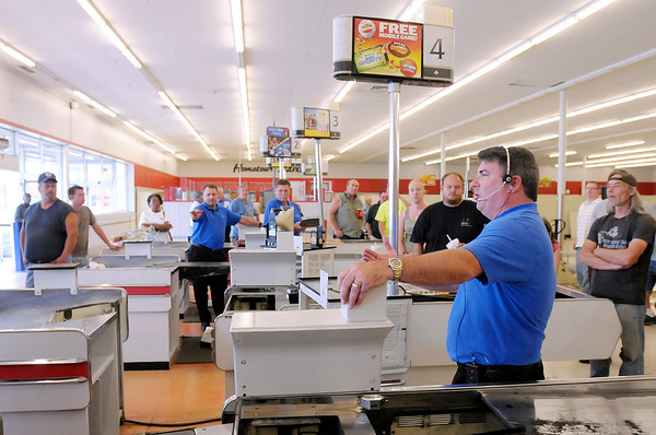 Judd Grafe, President of Grafe Auction, takes bids for the check out lanes during an auction in the former Marsh location on 53rd Street in Anderson on Monday.