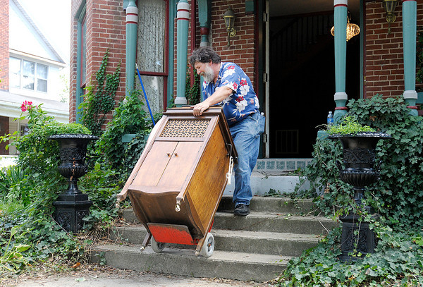 Torry Stiles of Indianapolis carefully moves an antique record player following an auction on West 8th Street on Saturday.