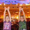 "From left, Kinley Hughes, 8, and Lizzi Horton, 7, raise their hands into the projector's beam of light to create butterflies on the screen as they wait for the movie ""The Lorax"" to start during the United Way Family Film Series at the Paramount on Thursday."
