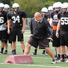 Anderson University head football coach Bobby Ladner goes through  a drill showing his defense what he wants during practice Monday.