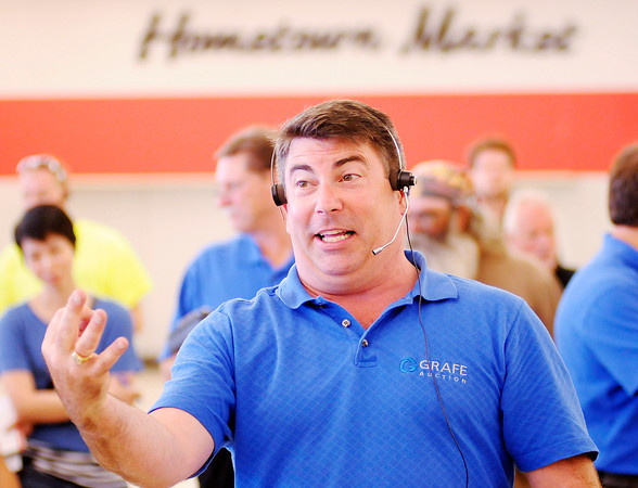 Judd Grafe, President of Grafe Auction, asks bidders for $3 as he auctions baskets during an auction in the former Marsh location on 53rd Street in Anderson on Monday.
