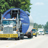 Indiana State Police officers escort a section of a windmill south on Indiana 37 to a staging area on Tuesday.