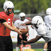 AU quarterback Mike Burel hands the ball off during drills at Monday's practice.
