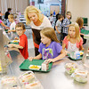 Third grade teacher April King asks Shelby Goyer, center, if she would like some fruit as from left, Cooper Gayle, Goyer and Allison Helmer go through the lunch line on the first day of school at Maple Ridge Elementary on Tuesday.