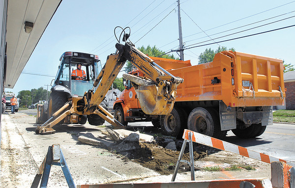 Anderson Street Department workers tear out the sidewalk on Vineyard Street just east of Broadway this past Wednesday to replace it.