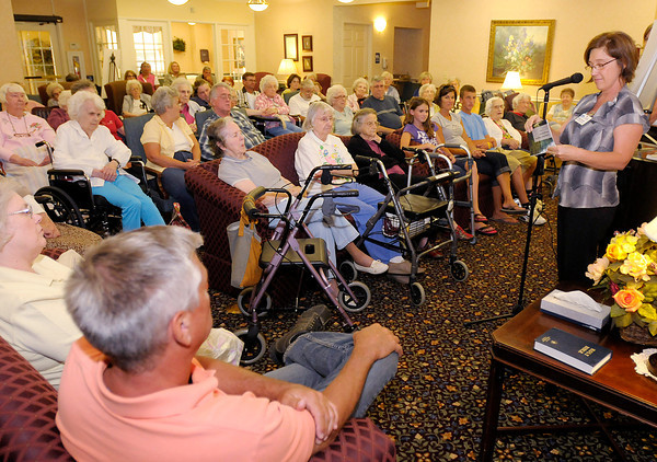 Director of Resident Programming Penny Stevens reads from a book of six word memoirs of Bethany Pointe residents during a book release and reception on Thursday.
