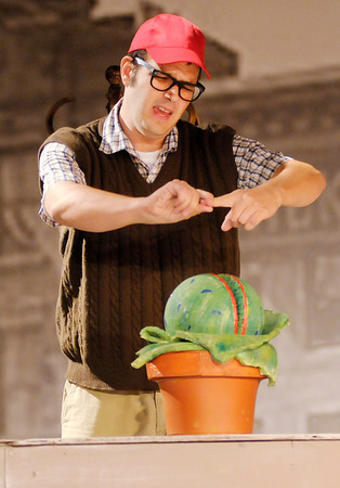 """Seymour (Tommy Thomas) feeds Audrey II his own blood during Mainstage's production of the """"Little Shop of Horrors."""""""